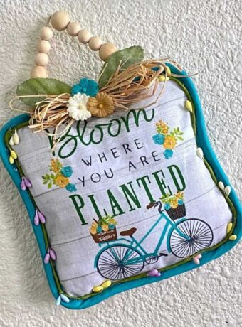 Dollar Tree 'Bloom Where you Are Planted' Pot Holder DIY Doorknob Hanger with a raffia bow and wood bead hanger.